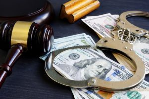 Handcuffs and gavel on stack of bills